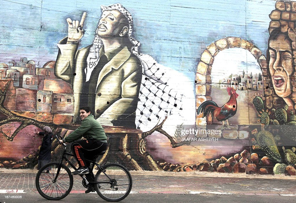 A Palestinian boy cycles past a mural painted by university students depicting the late Palestinian leader Yasser Arafat in the West Bank city of Nablus on November 9, 2013. The Palestinians said on November 8, that Israel is the only suspect in the 'assassination' of Yasser Arafat, a day after Swiss experts said tests suggested their veteran leader was killed by polonium poisoning. AFP PHOTO/JAAFAR ASHTIYEH