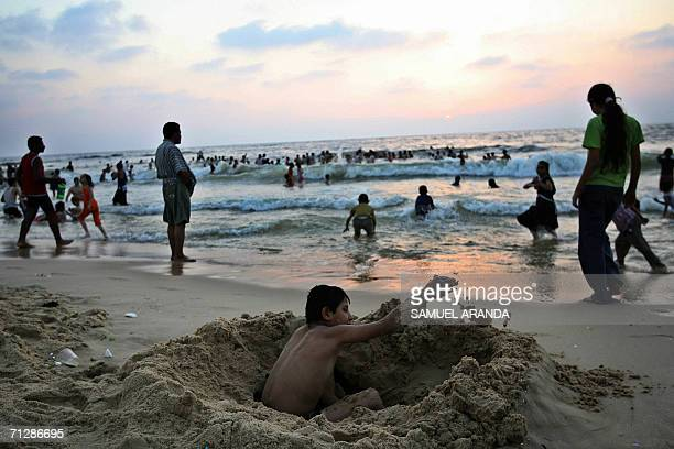 Palestinian boy dig in the sands as others swim at a beach in Gaza City 23June 2006 Palestinian president Mahmud Abbas was due in Gaza today for...