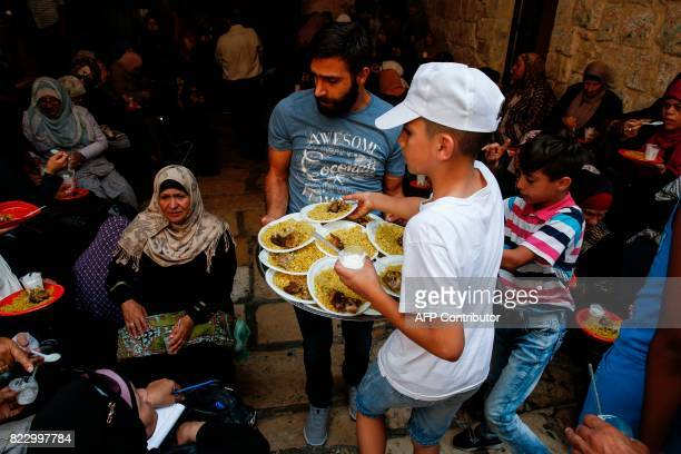A Palestinian boy distributes food donated to support demonstrators who have kept vigil for over a week as they pray outside AlAqsa mosque compound...