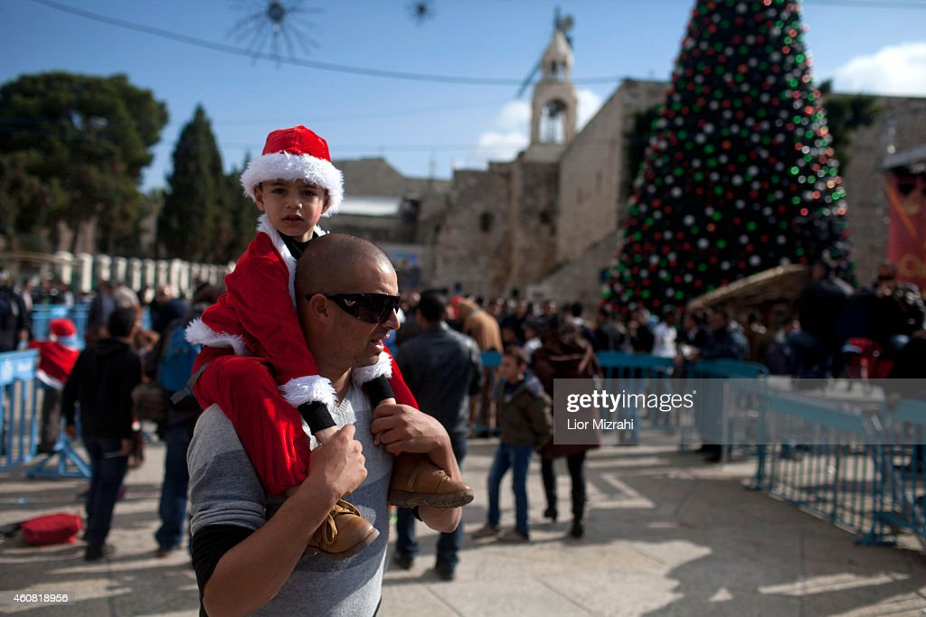 Palestinian boy dressed in a Santa Claus costume is seen outside the Church of the Nativity on December 24 2014 in Bethlehem West Bank Every...