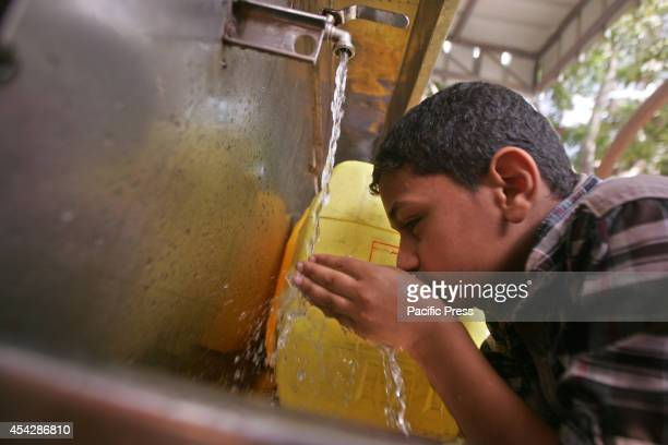 Palestinian boy drinking water from a desalination plant after the war ended officially in Rafah Southern Gaza strip