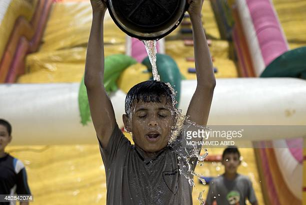 A Palestinian boy empties a bucket of water on his head during summer activities organized by the United Nations Relief and Works Agency in Gaza City...