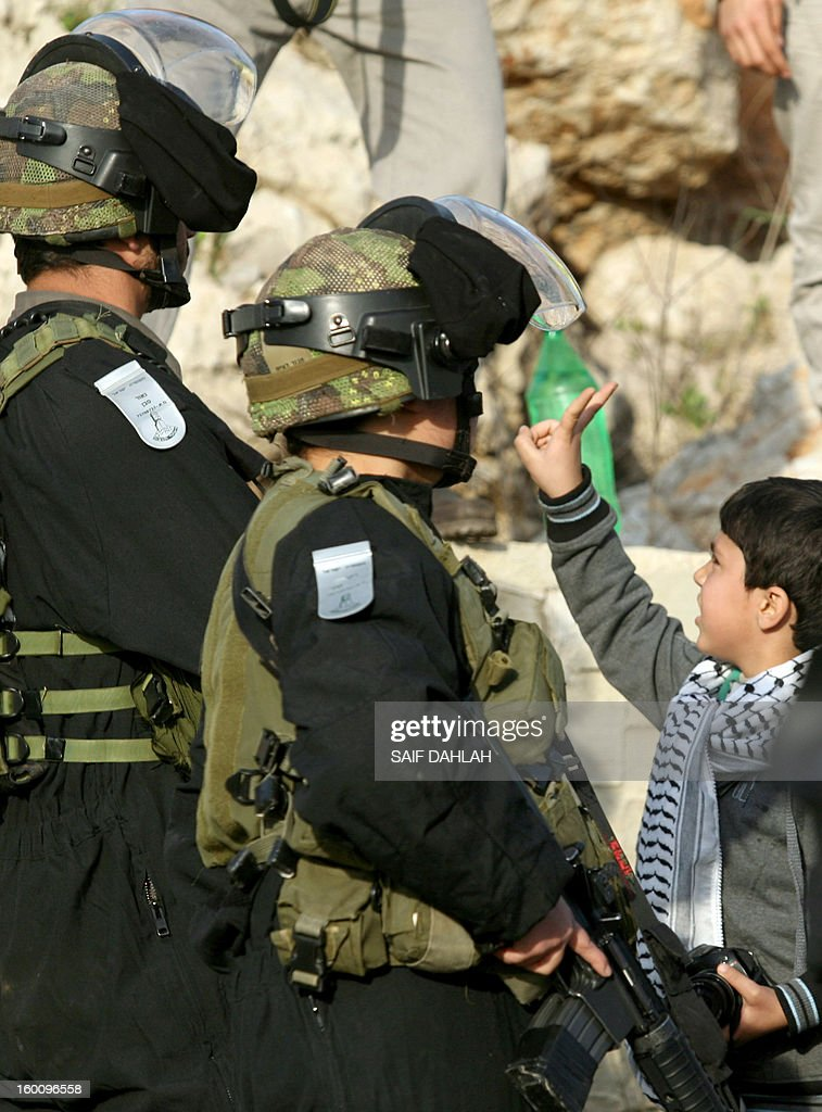 A Palestinian boy flashes a victory sign in front of Israeli soldiers during a protest in Anin village in the West Bank near Jenin city, on January 26, 2013. Protestors planned to erect a number of tents in solidarity with Palestinian prisoners in Israeli jails, a move they called 'Breaking the constraint'.