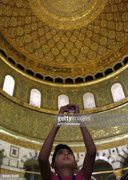 A Palestinian boy from the Gaza Strip takes a photo inside the Dome of the Rock mosque in the AlAqsa mosque compound in Jerusalem's old city on...