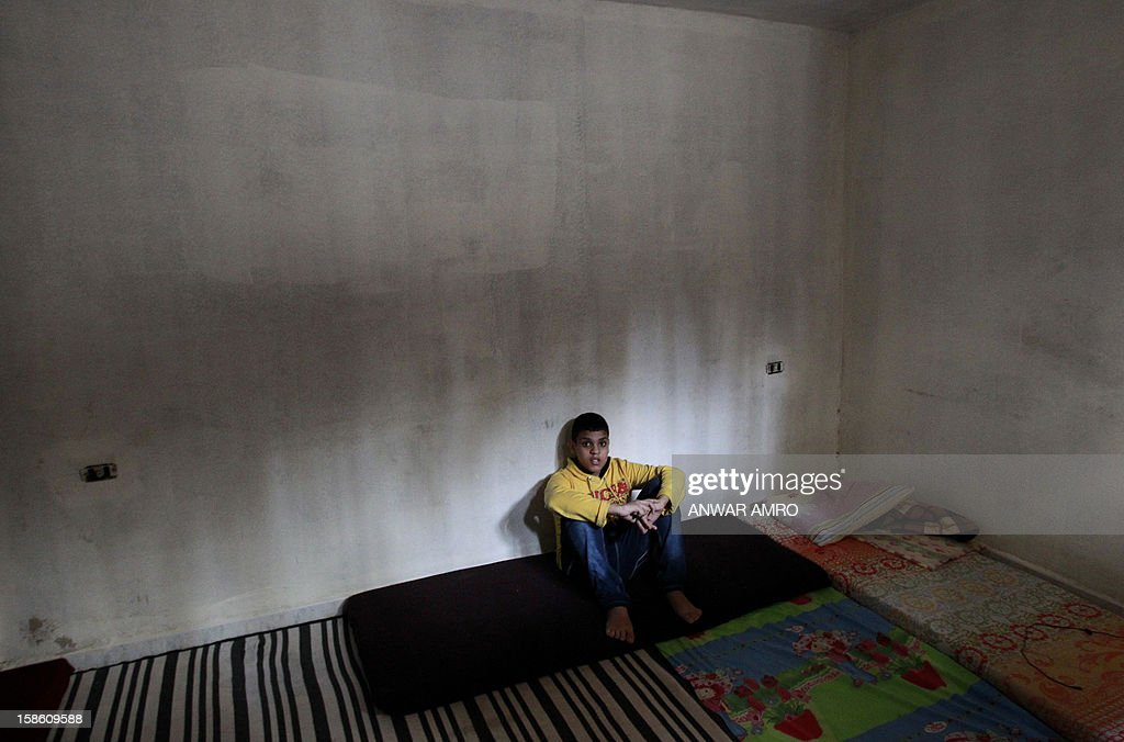 Palestinian boy from the Syrian refugee camp of Yarmuk sits in his family's temporary home at the Shatila refugee camp in the Lebanese capital Beirut on December 19, 2012. Some 13,000 members of Syria's Palestinian refugee community have gone back to square one in neighbouring Lebanon. Like their ancestors, they too have been forced to flee their birthplace into exile.