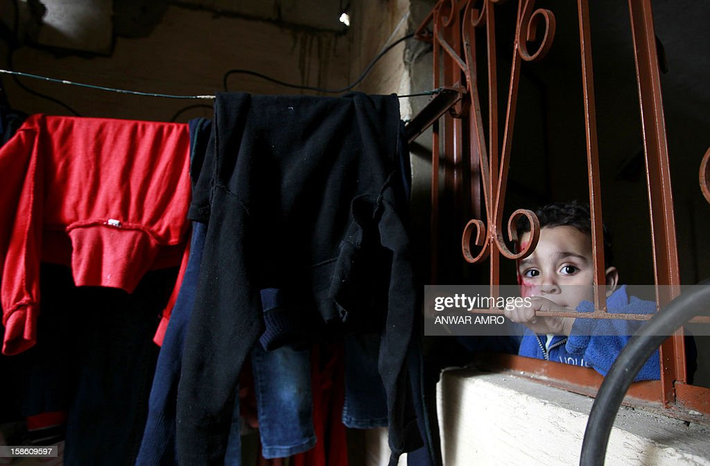 Palestinian boy from the Syrian refugee camp of Yarmuk stands behind the window of his family's temporary home at the Shatila refugee camp in the Lebanese capital Beirut on December 19, 2012. Some 13,000 members of Syria's Palestinian refugee community have gone back to square one in neighbouring Lebanon. Like their ancestors, they too have been forced to flee their birthplace into exile.