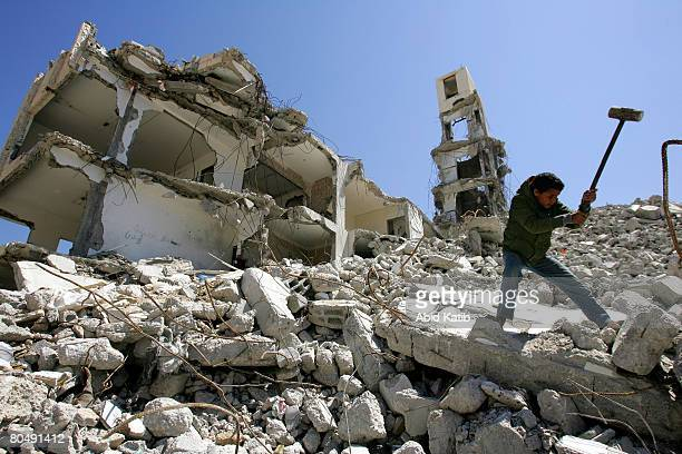 Palestinian boy hammers concrete in the rubble of the Interior Ministry building to extract iron and floor tiles to sell on April 2 2008 in Gaza City...