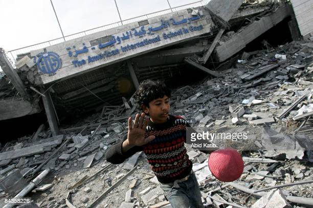 Palestinian boy holds a ball as he walks on the rubble of the American International School which was destroyed by an Israeli air strike January 19...