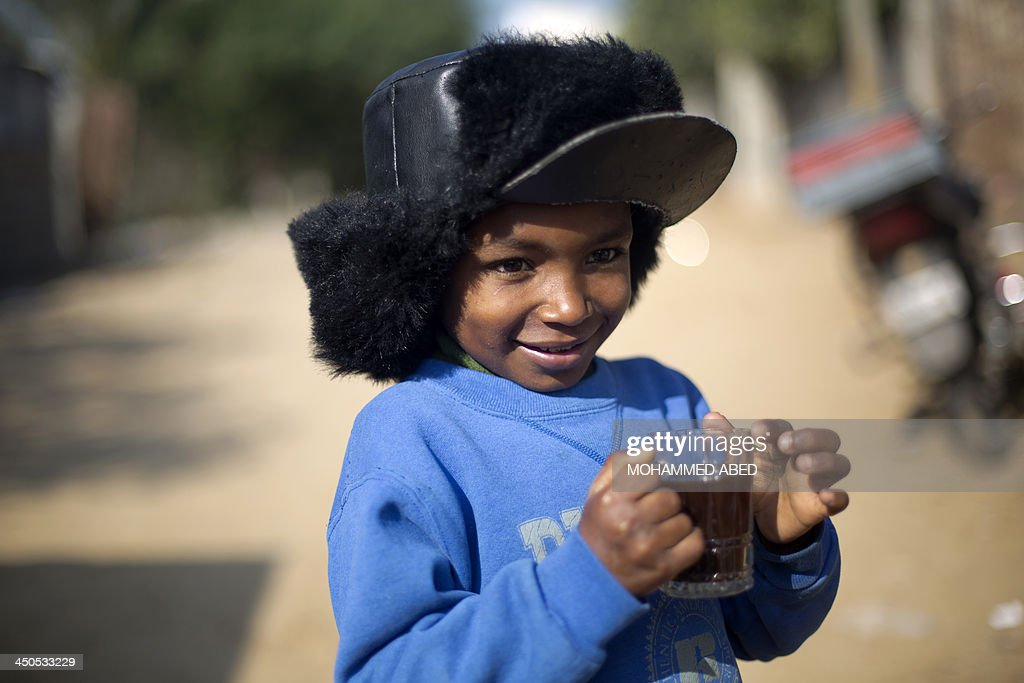 A Palestinian boy holds a cup of coffee in Biet Hanun northern Gaza Strip, on November 19, 2013. The Hamas run Palestinian territory is suffering a shortage in butane gas.