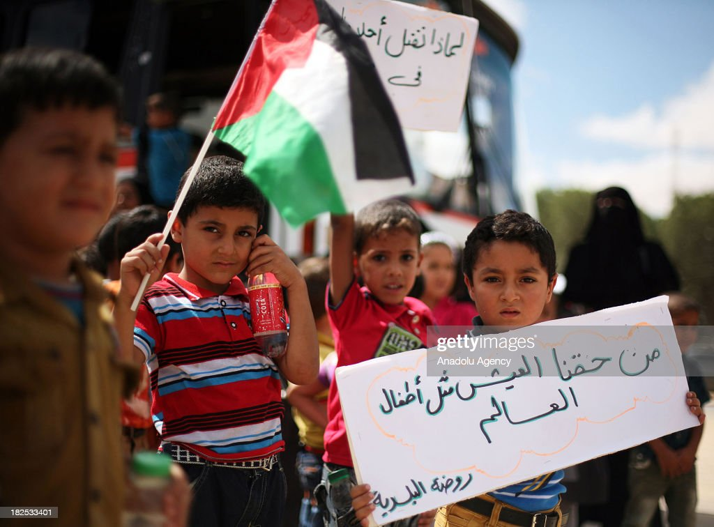 Palestinian boy holds a placard reading 'It's our right to live like other children in the world' during a demonstration at the Rafah border crossing between the Gaza Strip and Egypt on September 29, 2013 in Rafah town, southern Gaza strip. Hundreds of Palestinian children staged a demonstration on Sunday outside Rafah crossing with Egypt in protest of the long-time closure of the terminal by Egyptian authorities.