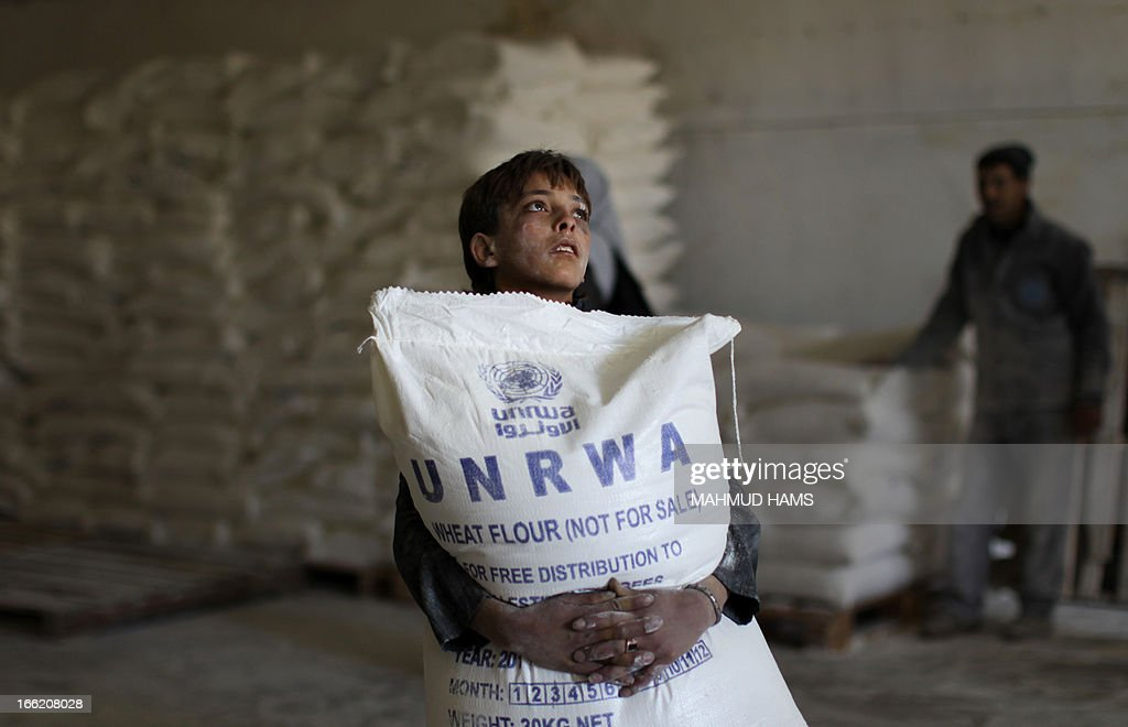 A Palestinian boy holds a sack of flour at a United Nations Relief and Works Agency (UNRWA) aid distribution centre in Gaza City on April 10, 2013. The United Nations reopened aid distribution centres in Gaza, after a four-day closure in response to the storming of its offices last week by protesters demanding reinstatement of a monthly cash allowance to poor families which was halted from April 1 due to budget cuts. AFP PHOTO/MAHMUD HAMS