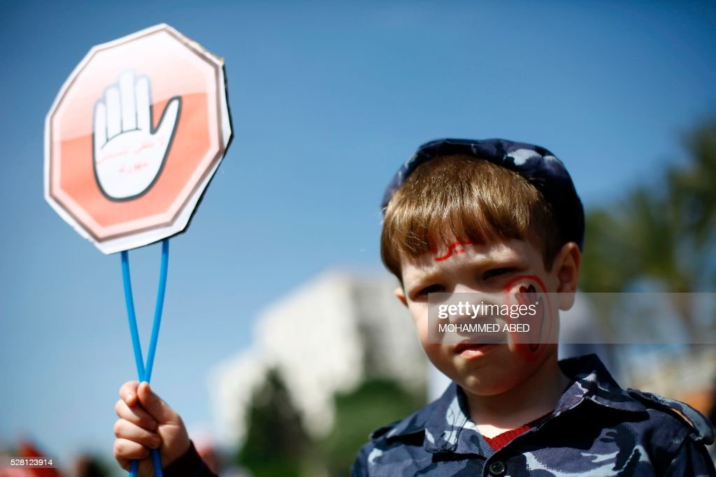 A Palestinian boy holds a stop sign during a day where the traffic police have increased presence in the streets to raise traffic awareness in Gaza City on May 4, 2016. / AFP / MOHAMMED