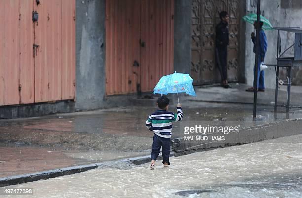 A Palestinian boy holds an umbrella as he walks through a flooded street in Gaza City on November 17 2015 AFP PHOTO / MAHMUD HAMS