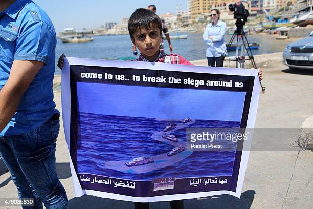 Palestinian boy holds banner during a protest against the Israeli blocking of a boat of foreign activists from reaching Gaza at the seaport of Gaza...