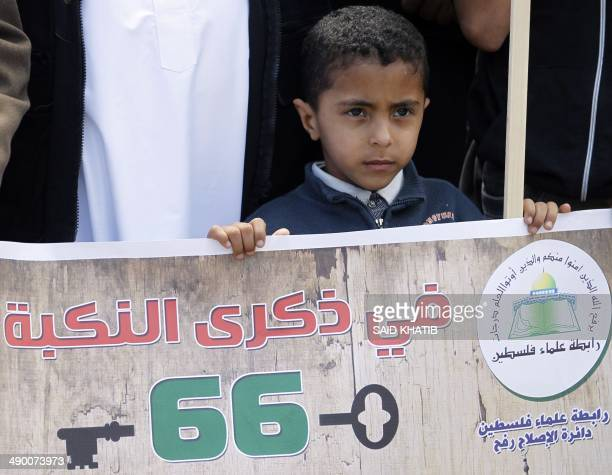 A Palestinian boy holds onto a banner that reads in Arabic 'In memory of the Nakba' during a rally marking the 'Nakba' on May 13 in Rafah town in the...