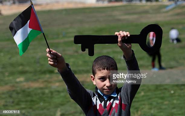 Palestinian boy holds up a key and a Palestinian national flag during a rally marking the 66th anniversary of the Nakba Day in Gaza city on May 13...