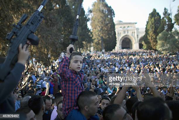 A Palestinian boy holds up a plastic gun during a demonstration against Israel's military offensive on the Gaza Strip on July 28 2014 at alAqsa...