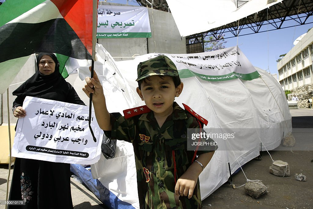 A Palestinian boy in military fatigues waves his national flag next to a woman holding a sign reading in Arabic 'Rebuilding the Nahr al-Bared refugee camp is the duty of the Arab nations and the world' as residents of the camp go on a hunger strike outside the headquarters of the UN Relief and Works Agency for Palestine Refugees (UNRWA) in the Lebanese capital Beirut on May 20, 2010. Refugees are demanding the reconstruction of their camp which was destroyed in clashes between the Lebanese army and radical Islamists in 2007.