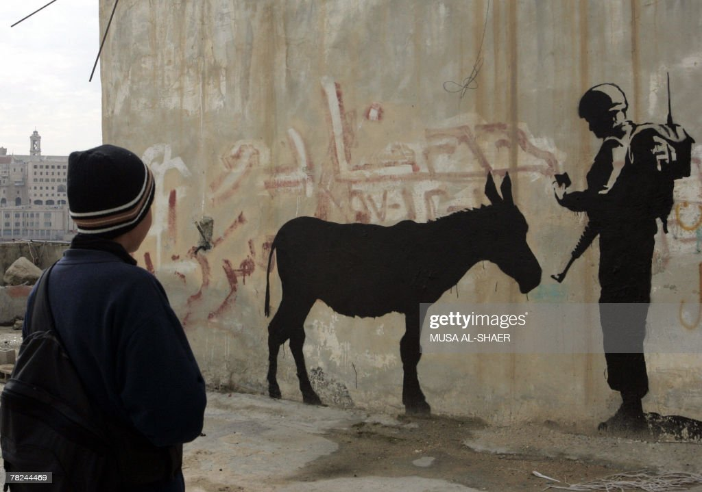 A Palestinian boy in the West Bank town of Bethlehem looks at graffiti depicting an Israeli soldier checking the ID of a donkey, a work by British artist Banksy, 04 December 2007. Banksy is a pseudonymn for an anonymous British aritist who has reached considerable celebrity.