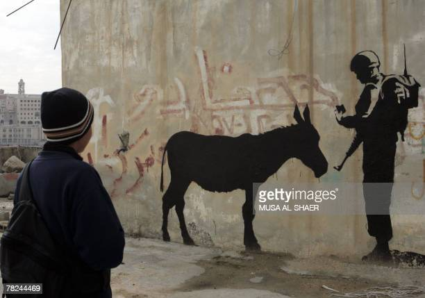 A Palestinian boy in the West Bank town of Bethlehem looks at graffiti depicting an Israeli soldier checking the ID of a donkey a work by British...
