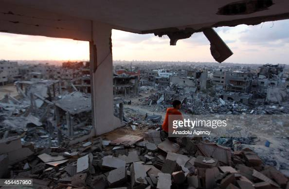 Palestinian boy is among the debris of destroyed buildings as Palestinians start to return their homes during ceasefire in alShaaf neighborhood Gaza...