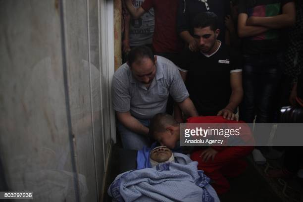 A Palestinian boy kisses the dead body of 23 years old Palestinian Eyad Gheith who allegedly carried a gun before killed by Israeli forces in Kiryat...
