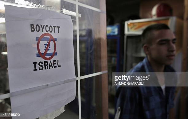 A Palestinian boy leaves a store that had erected a poster calling people to boycott Israel in east Jerusalem neighbourhood of Beit Hanina on August...