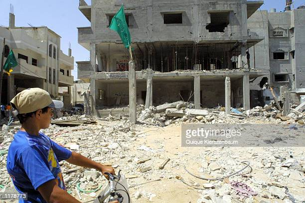 Palestinian boy looks at the destroyed buildings in Gaza City on July 26 2002 An Israeli warplane attacked a house in the Gaza Strip early Tuesday...
