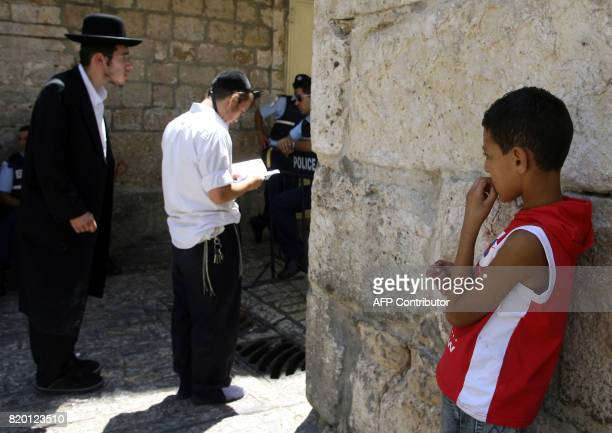 A Palestinian boy looks on as Ultra Orthodox Jews pray at one of the entrances of the alAqsa mosque compound during the Jewish Tisha 'Av...
