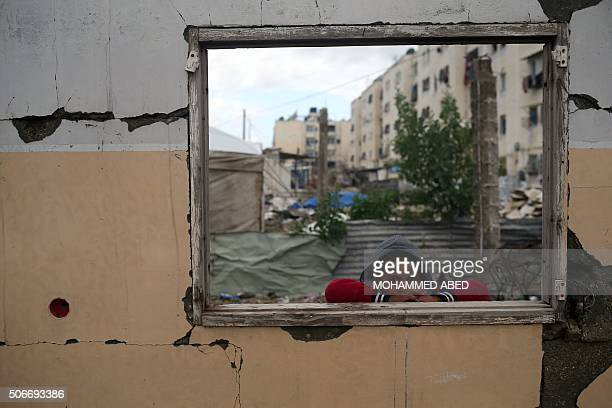 Palestinian boy looks on from the window of a building that was destroyed during the 50day war between Israel and Hamasled militants in January 2015...