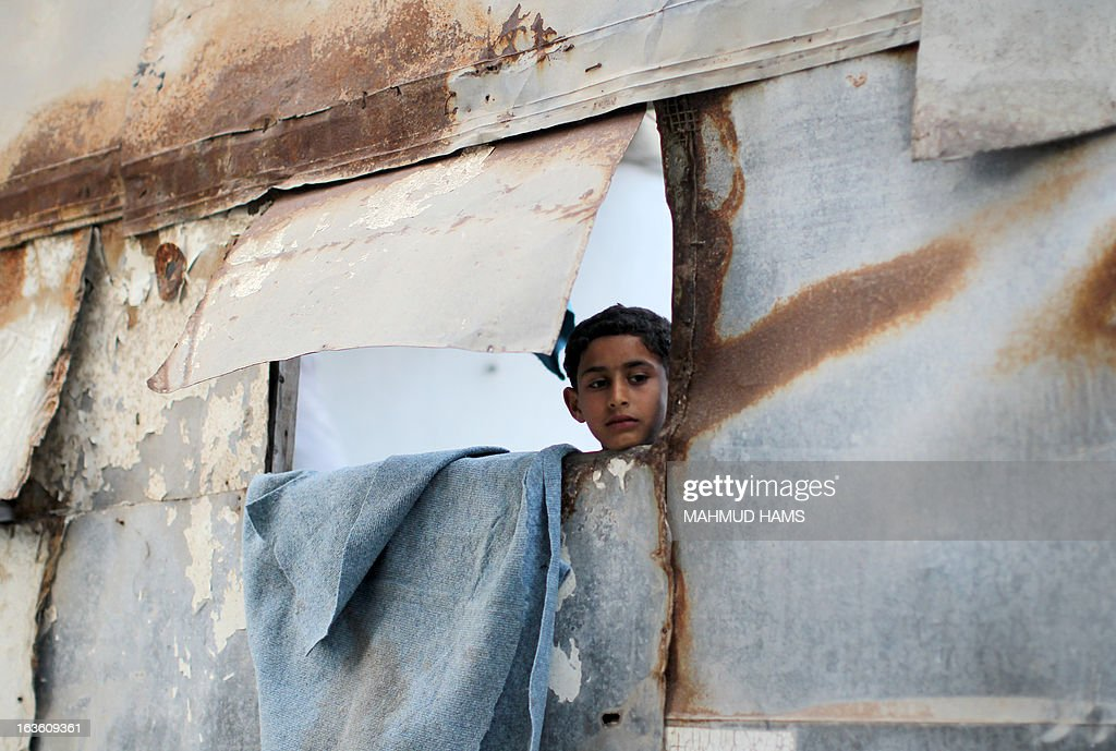 A Palestinian boy looks out of the window of this tin fabricated home in the Mediterranean beachfront al-Shati Palestinian refugee camp, the third largest in the Palestinian Territories, in Gaza City on March 13, 2013. AFP PHOTO / MAHMUD HAMS
