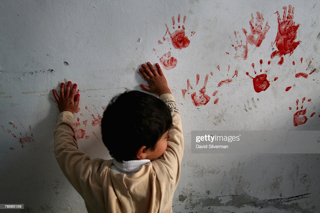 A Palestinian boy makes hand prints on the walls of his home from the blood of a just-slaughtered sheep at the start of Eid al-Adha in al-Azza refugee camp December 19, 2007 in Bethlehem in the West Bank. The biblical town is celebrating both Christmas and the Muslim Feast of the Sacrifice over the next week.