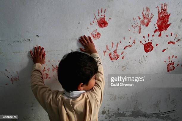Palestinian boy makes hand prints on the walls of his home from the blood of a justslaughtered sheep at the start of Eid alAdha in alAzza refugee...