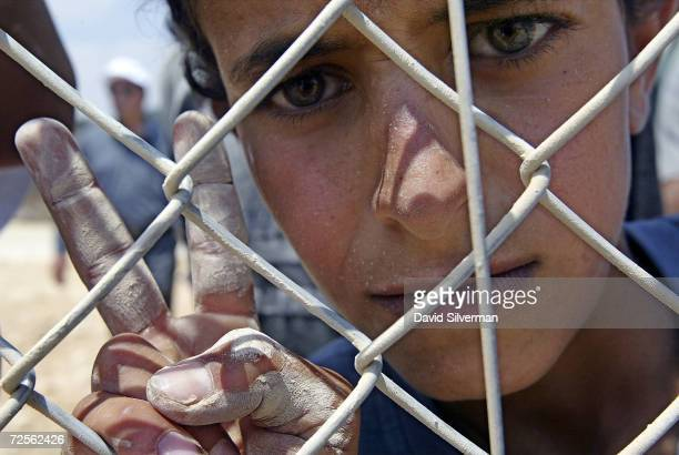 Palestinian boy makes the victory sign as he looks through Israel's security fence July 28 2003 next to the northern West Bank Palestinian village of...