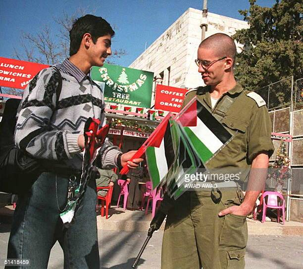Palestinian boy offers a Palestinian flag to one of the last Israeli officers remaining in Bethlehem on the West Bank 20 December The birth town of...