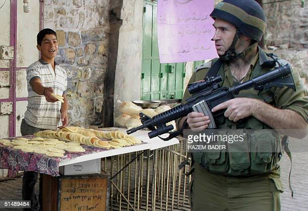 Palestinian boy offers an Israeli soldier 'Qataiyef' a traditional Arab sweet made for Ramadan while on patrol in the divided West Bank city of...