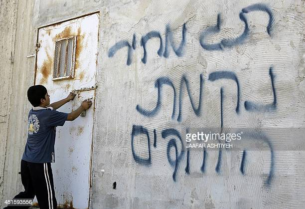 A Palestinian boy opens a door after Hebrew graffiti was daubed on a wall allegedly by Jewish settlers in the village of Aqraba in the Israeli...