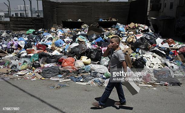 A Palestinian boy pinches his nose as he walks past piles of accumulated rubbish in the Palestinian refugee camp of Shuafat in east Jerusalem on June...