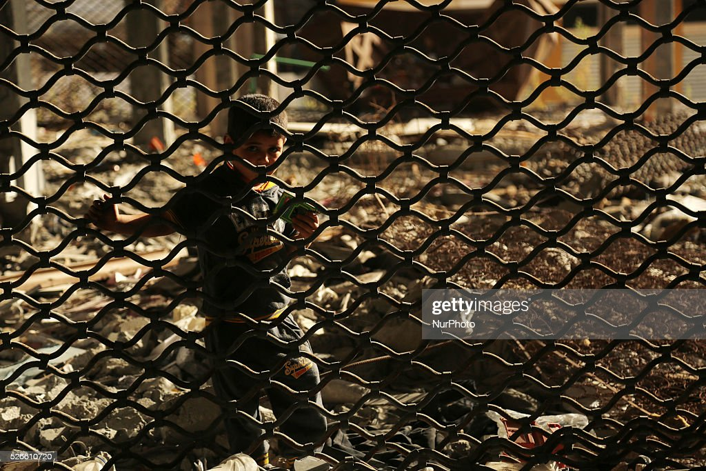 A Palestinian boy play on the rubbles of houses, which were destroyed during the recent Israeli war 2014, in Gaza city, on April 30, 2016. Israels punitive ban on cement imports into the Gaza Strip has prevented hundreds of families from rebuilding their homes devastated by the 2014 war, the UN Office for the Coordination of Humanitarian Affairs (OCHA) said in a press release Thursday.