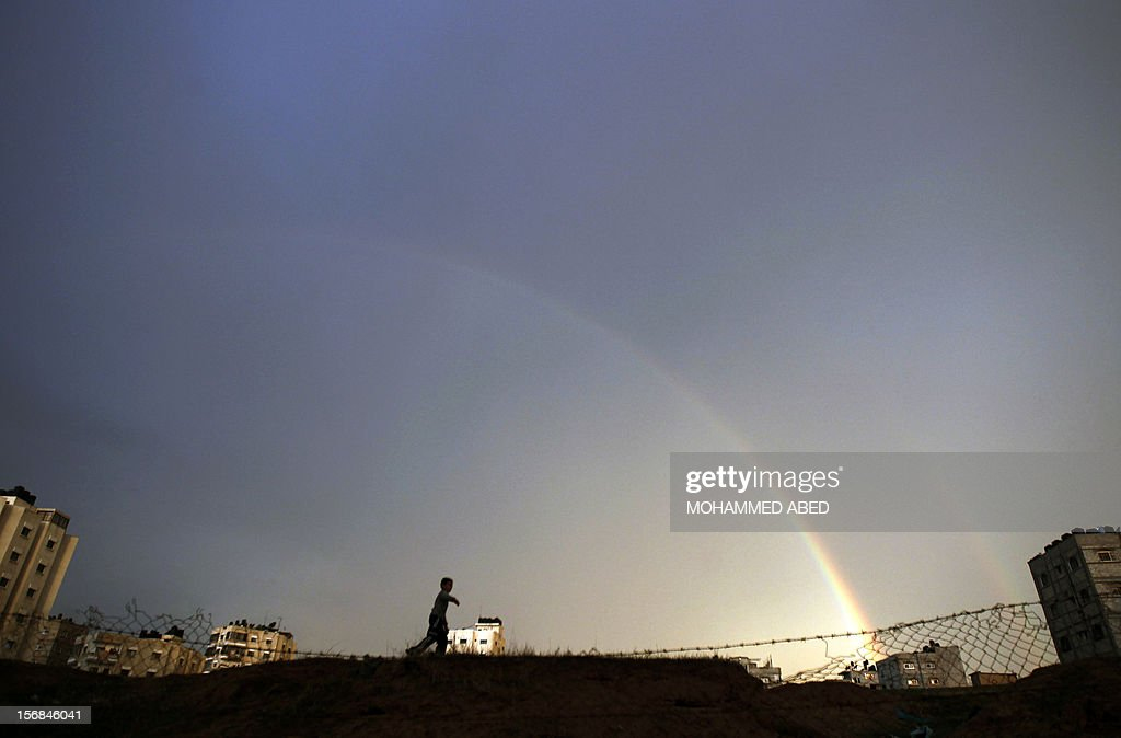 A Palestinian boy plays as a rainbow arcs over Gaza City on November 23, 2012. Israeli politicians returned to the campaign trail as the streets of Gaza came back to life after a truce ended eight days of bloodshed, with both sides claiming victory while remaining wary. AFP PHOTO/MOHAMMED ABED
