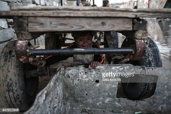 Palestinian boy plays under a donkey cart outside his house in an impoverished area in the southern Gaza Strip town of Khan Yunis on February 19 2017...