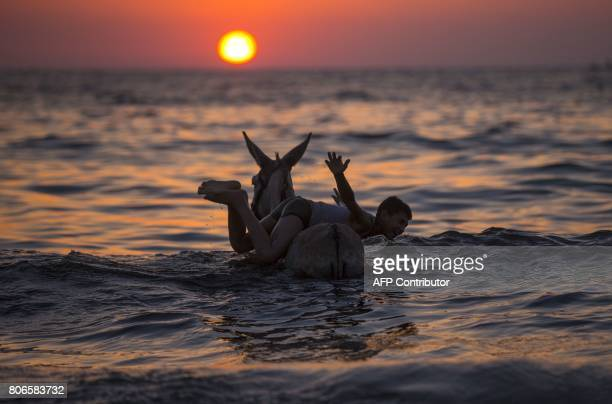 Palestinian boy plays with a donkey in the sea at sunset in Gaza City on July 3 2017 / AFP PHOTO / MAHMUD HAMS