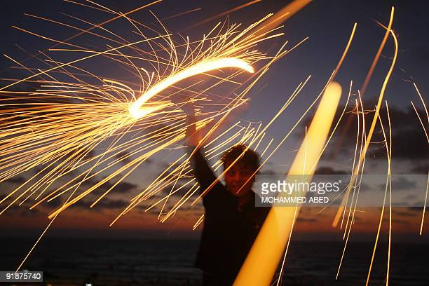 A Palestinian boy plays with a sparkler on the eve of the Muslim holy fasting month of Ramadan in Gaza City on August 21 2009 Starting on August 22...