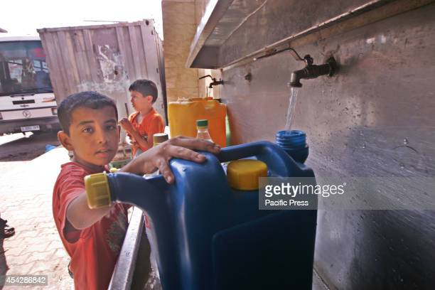 Palestinian boy pours water into a container from a desalination plant after the war ended officially in Rafah Southern Gaza strip