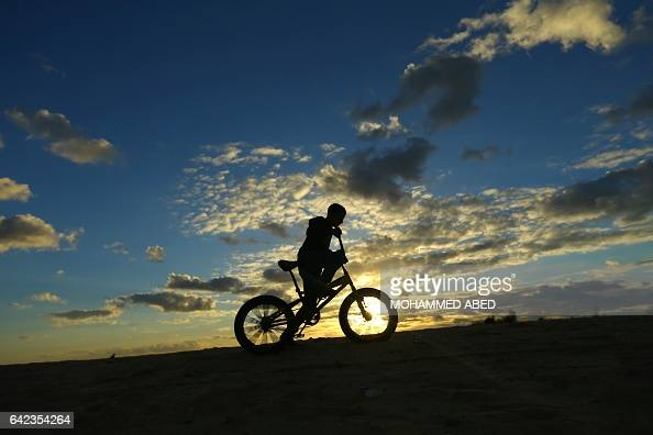 Palestinian boy rides a bicycle during sunset in Rafah in the southern Gaza Strip on February 17 2017 / AFP / MOHAMMED ABED