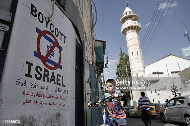 A Palestinian boy rides his bicycle past past a mural calling people to boycott Israeli goods in the alAzzeh refugee camp near the West Bank city of...