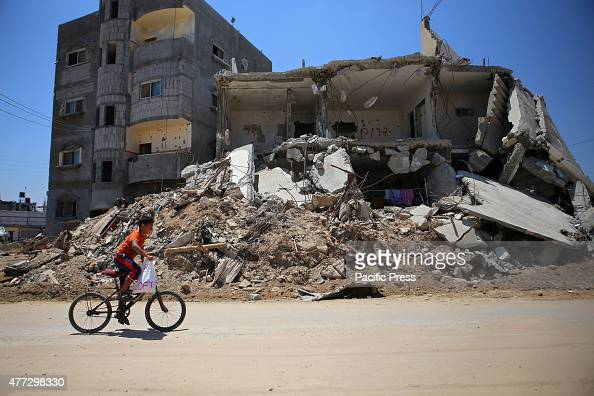Palestinian boy rides his bicycle past the rubble of buildings which were destroyed during the 50day war between Israel and Hamas militants in the...
