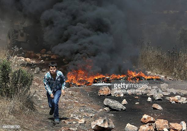 A Palestinian boy runs amid the smoke of burning tires during clashes between Palestinian protesters and Israeli security forces following a...