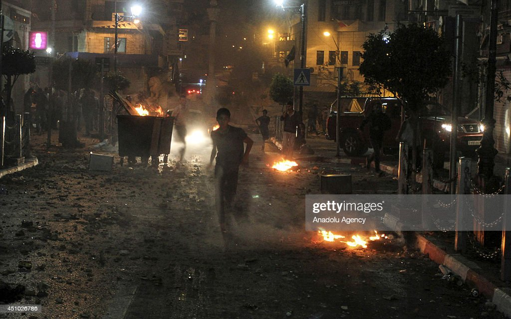 A Palestinian boy runs for cover during clashes with Israeli security forces taking part in the search for three missing teenagers in Ramallah, West Bank on 22 June, 2014. Palestinians protest the operation of Israeli soldiers to locate the three teenagers who are believed to abducted by Islamist movement Hamas on 12 June.
