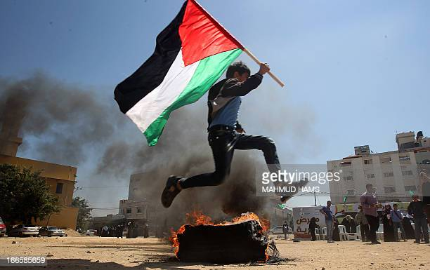 A Palestinian boy runs holding his national flag near a burning tyre as he acts out a scene for spectators visiting a building which used to be an...